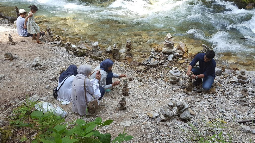 people stacking rocks in Vintgar gorge
