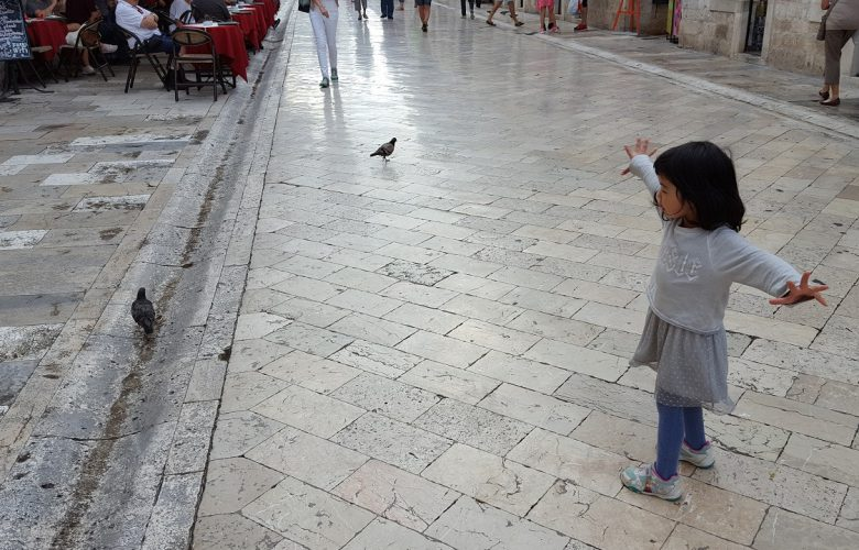 little girl with pigeon in dubrovnik old town