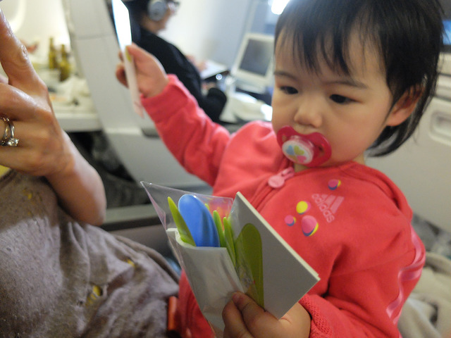 baby playing plastic forks on the plane