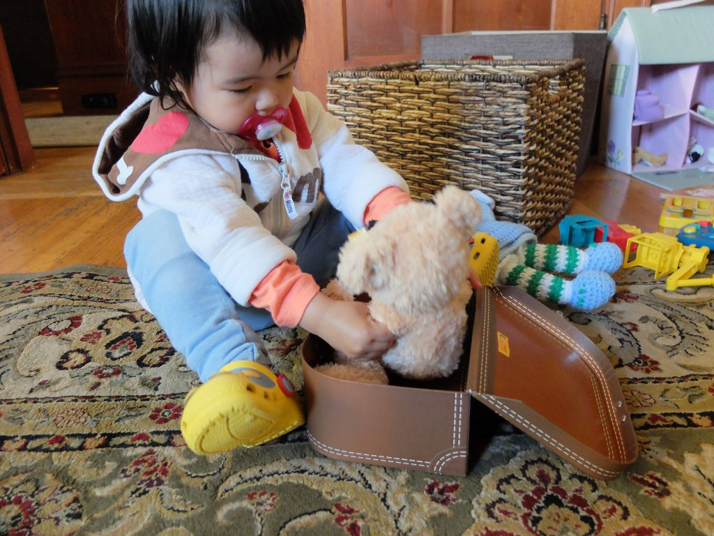 toddler packing the teddy bear