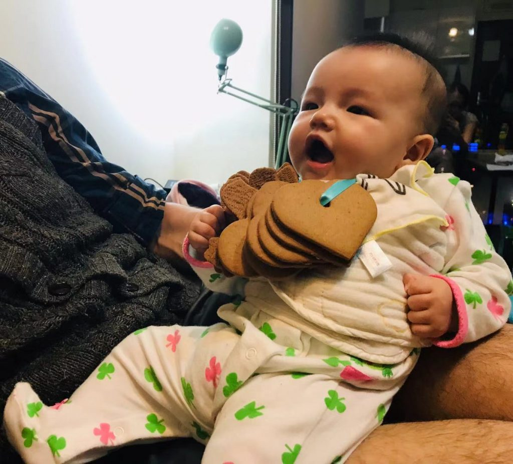 baby with cookies around the neck